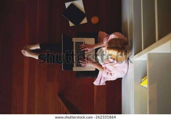Top view young female freelancer busy working on laptop computer while leaning on home bookshelf sitting on the floor, charming business woman working from home while having breakfast, young student