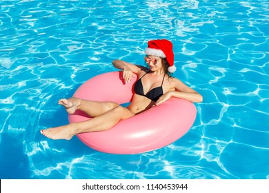 top view of young female in Santa Claus hat swim with pink circle in pool.