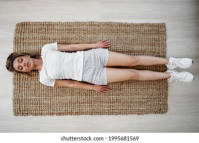 Top view of a young fit girl exercising on a mat at home