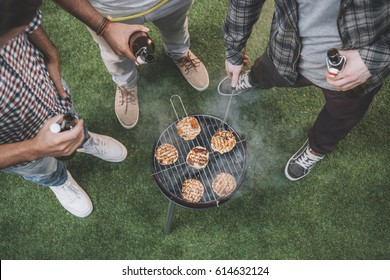 top view of young friends drinking beer and making barbecue