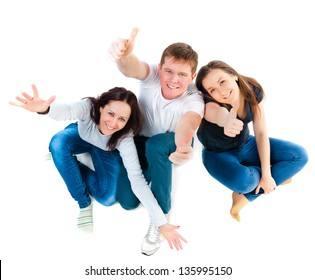 Top view of young friends sitting on the floor and showing thumbs up