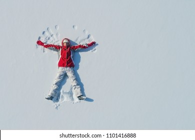 Top view of young girl is lying on the snow and making angel wings. Copy space.