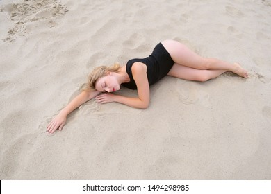 Top view of a young girl sleeping in a swimsuit on the beach