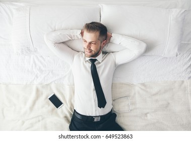 Top view. Young handsome businessman relaxing on bed after a tough day at work
