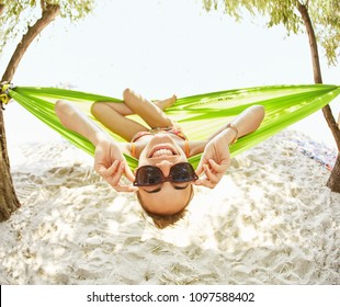 top view of a young happy woman in black sunglasses lying in a a bright green hammock on the beach. Wide angle picture
