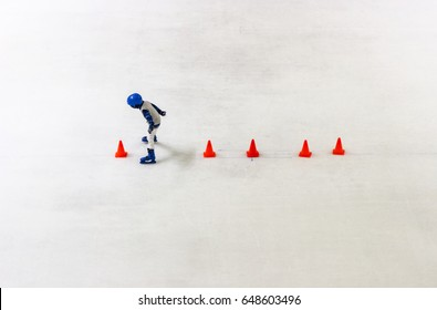 Top view young little boy learning to play ice skating with cones line