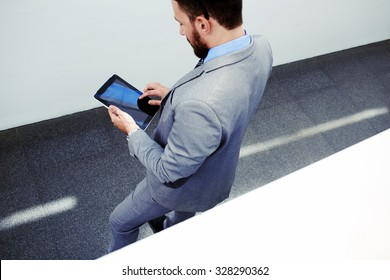 Top view of young male manager dressed in grey expensive suit holding touch pad with blank copy space screen for text,successful man in formal wear reading news on his digital tablet during work break