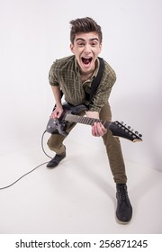 Top view of young male musician is playing a six-string bass guitar in studio.