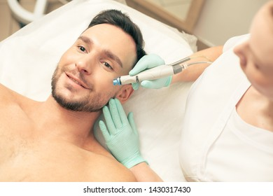 Top view of a young man expressing joy while lying on the pillow and cosmetologist nourishing his skin on the cheek with a help of a modern device