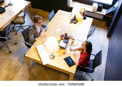 Top view - young man in formal suit and glasses and girl designer in red jacket discussing new project while working in large office. Co-working.