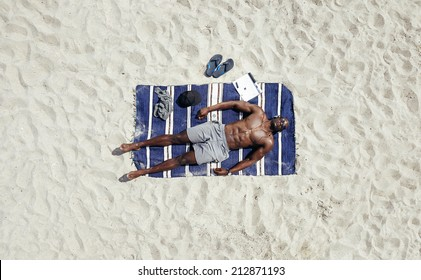 Top view of young man lying shirtless on a beach mat. African male model sunbathing.