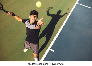 Top view of young man playing tennis tossing up the ball for the serve. Tennis player serving the ball in a match.