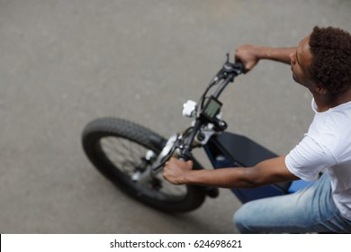Top view of young man riding electric bike along the road, selective focus