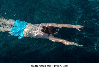 Top view at young man swimming under water.