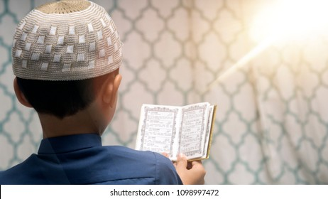 Top view of young muslim boy reciting Quran / Koran during the holy month of Ramadan. Toned image