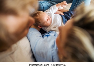 Top view of young parents with a newborn baby at home.