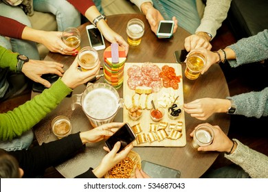 Top view of young people toasting beers and eating some snack aperitif at pub bar restaurant - Friends using mobile phones at pre dinner meeting - Focus on right bottom hand half pint - Warm filter
