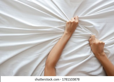 Top view young sexy woman hands pulling white sheets in ecstasy in hotel. Cute girl doing sign orgasm on white bed (sex and erotic concept for advertisement)