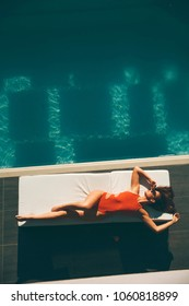 Top view at young slim beautiful woman in swimsuit sunbathing near swimming pool