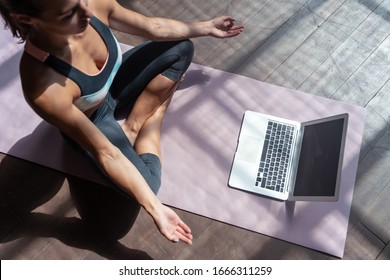 Top view young sporty slim woman coach internet video online training hatha yoga instructor modern laptop screen meditate Sukhasana posture relax breathe easy seat pose gym healthy lifestyle concept.