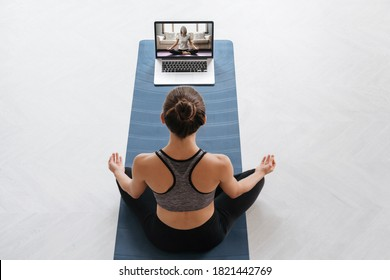 Top view young sporty woman using laptop for training hatha yoga with virtual instructor, doing Sukhasana, relax and breathe easy. Online fitness, workout at home. Wellness, active lifestyle concept