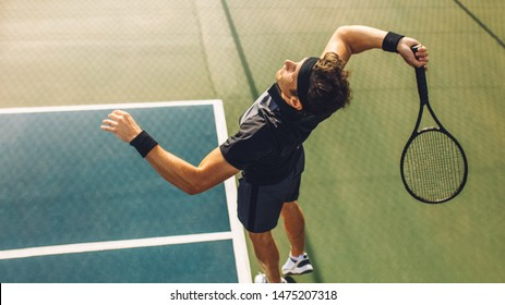 Top view of young tennis player jumping to hit the ball from the baseline of a hard court. Professional tennis player about to hit the ball for the serve.