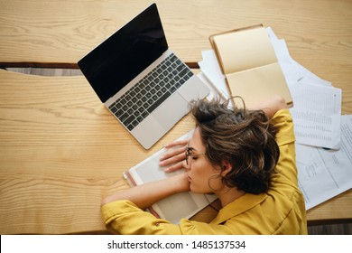 Top view of young tired woman fall asleep on desk with laptop and documents under head at workplace