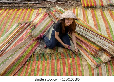 Top view of young Vietnamese craftsman making the traditional vietnam mats with happiness action in the old traditional village at dinh yen, dong thap, vietnam, tradition artist concept