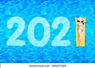 Der Blick auf die junge Frau in Bikini auf dem aufblasbaren Schwimmer mit der Nummer 2021 im Schwimmbad