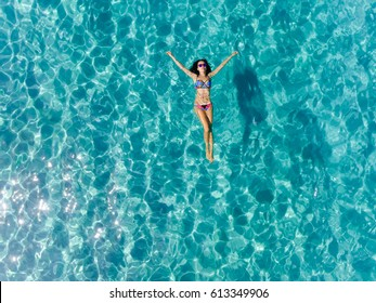 Top view of young woman in a bright bikini is swimming in the transparent, blue sea. Aerial view of slim woman lying and floating on the water of Andaman sea. Phuket, Thailand.
