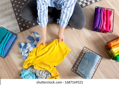 Top view a young woman in casual clothes stacks things, sorting them by colors and folding them into a metal mesh basket. Concept of smart tidy and cleanliness in the house