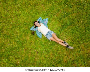 Top view of young woman in a checkered shirt who relaxing on the grass on the round towel. Towel looks like watermelon from above.