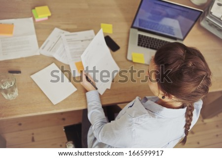 Top view of young woman checking bills while sitting at the desk with laptop. Caucasian businesswoman working at the desk.