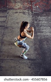 Top view of a young woman crouching on concrete background. Fit female in sportswear training on urban background. Woman doing squats outdoors.