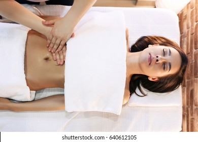 Top view of Young woman having abdomen massage. Masseur make massage for stomach