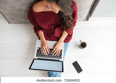 Top view of a young woman holding laptop computer on her lap while sitting at home