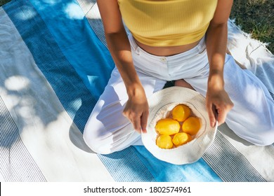 Top view of a young woman holds white headwear with lemons. Girl in white pants and yellow jersey holding a cotton basket of fresh-picked lemons sitting on the picnic blanket on a sunny day outdoors.