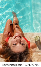 Top view of young woman with legs in a swimming pool with sunglasses in hand watching in camera top view
