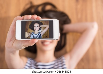 Top view of young woman is lying on the floor and is holding a cellphone.