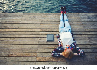 Top view young woman lying on a wooden jetty enjoying the sunshine,tourist girl in bright glasses lying on jetty by river, vintage photo of relaxing young woman in nature with tablet, cross process