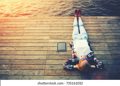 Top view young woman lying on a wooden jetty enjoying the sunshine,tourist girl in bright summer glasses lying on jetty by river, vintage photo of relaxing young woman in nature with tablet, flare sun