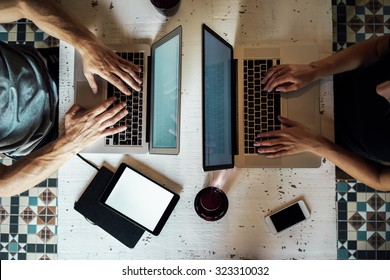 top view of a young woman and a young man who works with a laptops. phone and tablet on the table.  digital tablet with blank copy space screen for your information