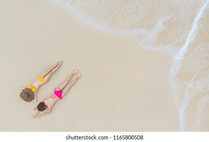 Top view Young woman in a pink bikini lying and relaxing on the white sandy beach with turquoise sea water of thailand,aerial view from drone / Summer concept.