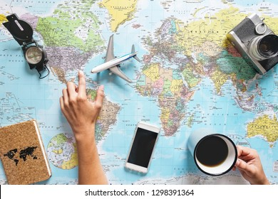 Top view of young woman planning her vacation using world map while drinking coffee - Tourist pointing the next travel destination - Concept of adventure, tourism, and traveling people lifestyle