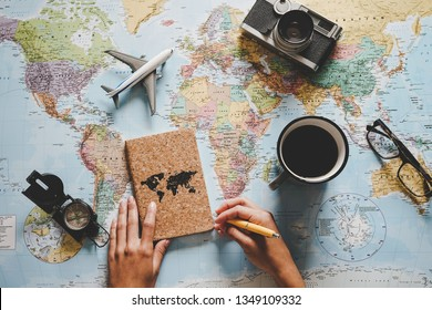 Top view of young woman planning her vacation using world map - Travel  influencer looking for the next travel destination - Concept of adventure, tourism, and traveling people lifestyle