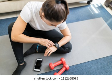 Top view of young woman sitting on yoga mat in living room and setting her smartwatch before workout at home