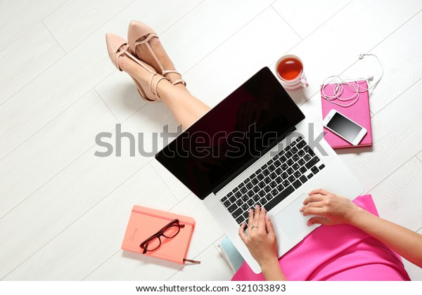 Top view of young woman sitting on floor with laptop