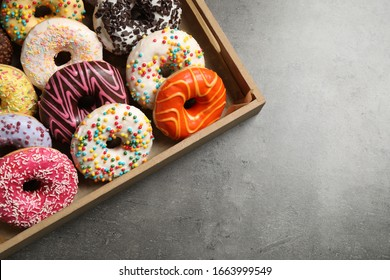 Top view of yummy donuts with sprinkles in box, space for text