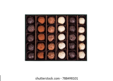 Top view of yummy tasty white, dark and milky chocolate balls in green box, isolated on white background.