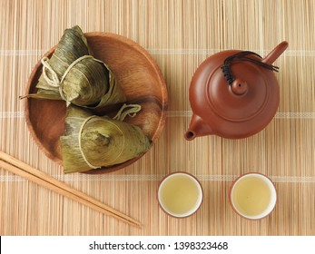 Top view of zongzi also called  rice dumplings or sticky rice dumplings on wooden mat background. Dragon boat festival is a traditional festival of East Asian culture. Chinese tea. Food concept.